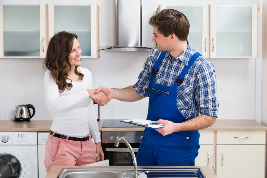 Young Woman Shaking Hands with Male Plumber With a Clipboard In the Kitchen