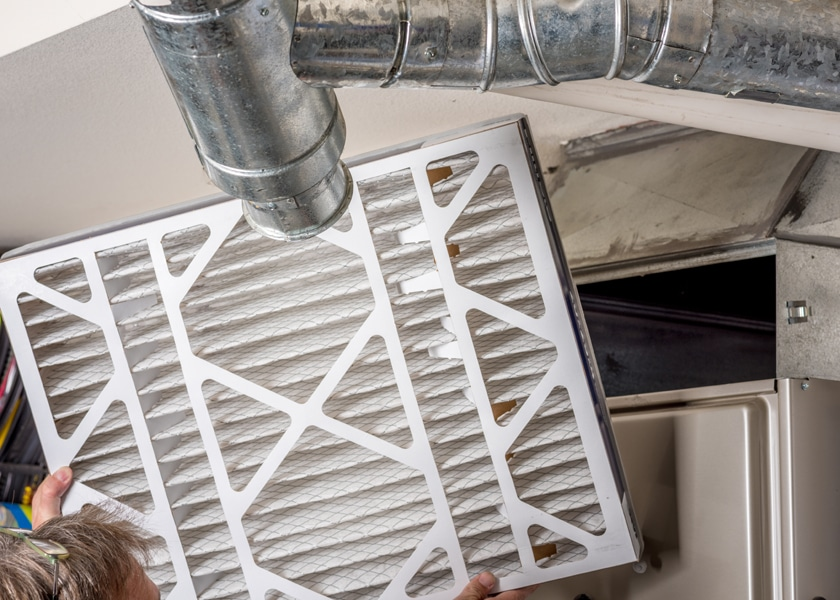 Handyman inspects a filter from a home furnace